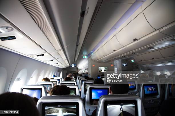 Inside of a long distance new airplane with passengers sitting and resting during a long flight with picture taken from the back of the airplane.