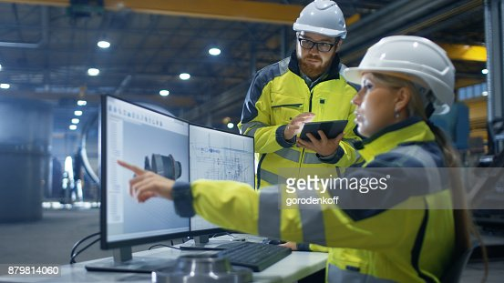Inside the Heavy Industry Factory Female Industrial Engineer Works on Personal Computer She Designs 3D Turbine Model, Her Male Colleague Talks with Her and Uses Tablet Computer. : Stock Photo