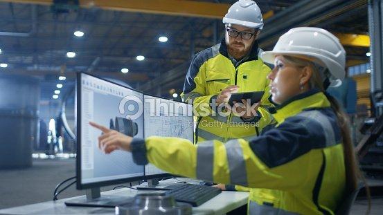 Dentro de la fábrica de industria pesada mujer Ingeniero Industrial trabaja en ordenador Personal ella diseños 3D turbina modelo, su colega masculino habla con ella y utiliza la computadora de la tableta. : Foto de stock