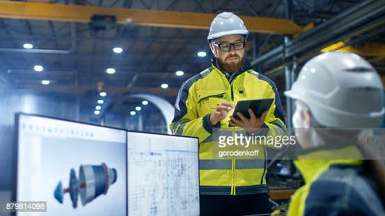 Inside the Heavy Industry Factory Female Industrial Engineer Works on Personal Computer She Designs 3D Engine Model, Her Male Colleague Talks with Her and Uses Tablet Computer. : Stock Photo