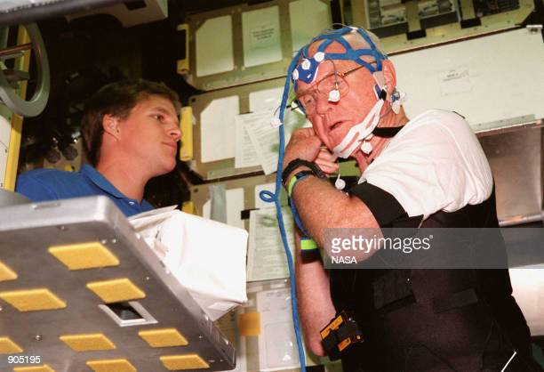Inside the SPACECHAB training module STS95 Payload Specialist John Glenn who is a senator from Ohio tries on the mesh cap that he will wear on the...