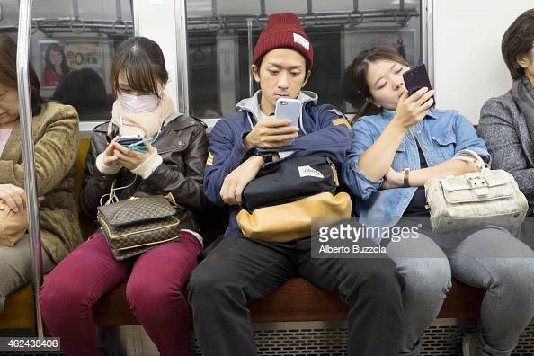 Inside the Tokyo subway commuters are often busy playing with their electronic devices such as tablets and smart phones