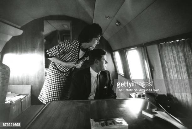 Inside their private plane married couple Jacqueline Kennedy and Senator John F Kennedy looking out a window at supporters on the tarmac during a...