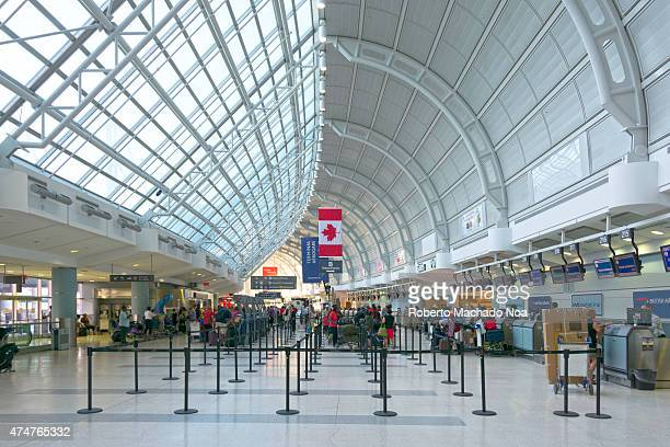 Inside view of the huge metal framed Lester B Pearson international airport People standing in queues with their baggage at the ticketing counters