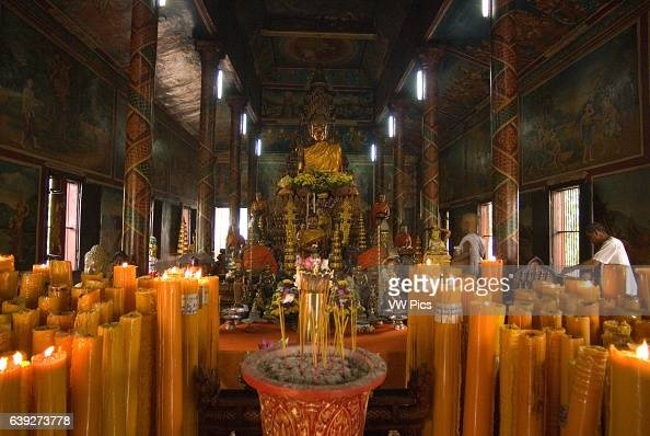 Inside Wat Phnom Phnom Penh Cambodia Candles and Buddha statue in Wat Phnom Phnom Penh Cambodia Wat Phnom is a Buddhist temple located in Phnom Penh...