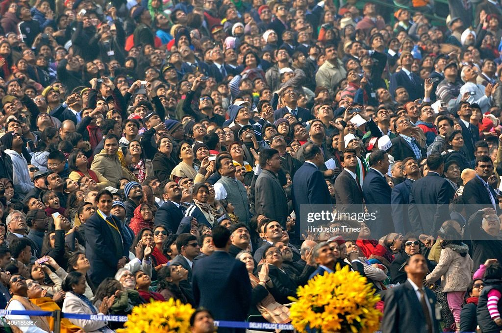 Inspectators looks up to see Airforce fighter aircrafts performance during the 65th Republic Day parade at Rajpath on January 26 2014 in New Delhi...