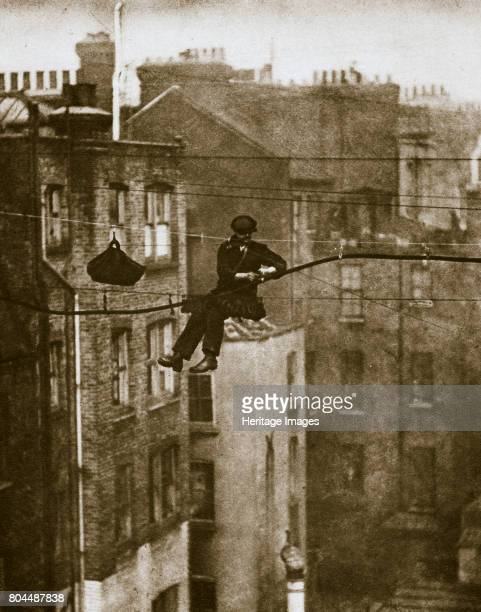 Inspecting a telephone cable between Conduit and Maddox Streets London 20th century The cables are fastened to the wires by rawhide suspenders and...