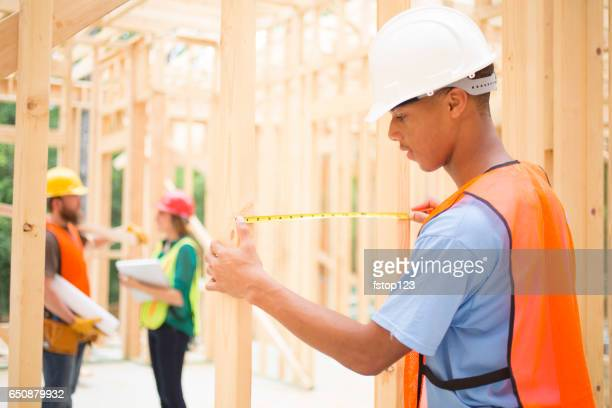 Inspector checks frame in building site.