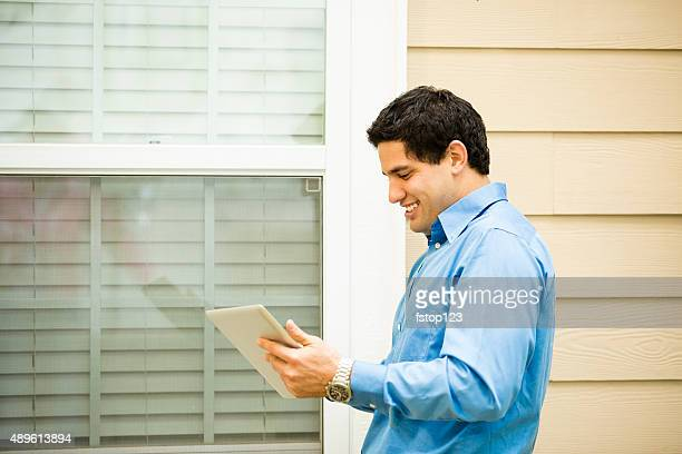 Inspector, engineer examines building wall, window outdoors.  Digital tablet.
