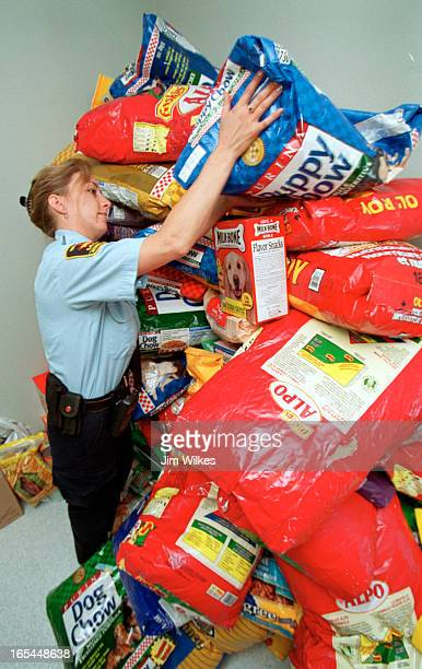 SPCA inspector Mindy Hall lifts a bag of dog food onto an every growing pile at the organization's Newmarket offices Score of people have donated...