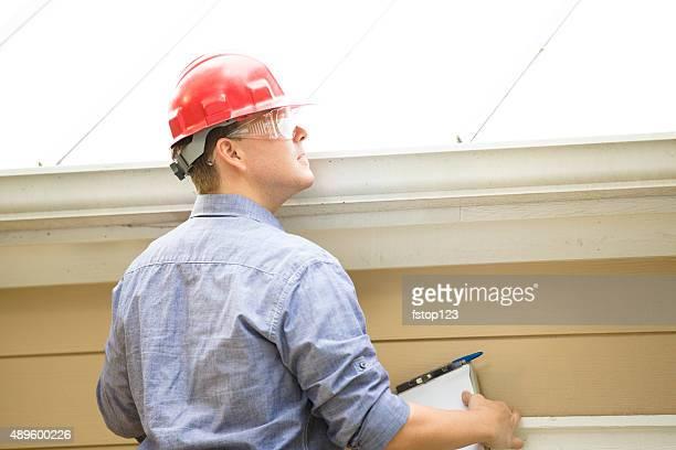 Inspector ou Trabalhador de IndústriaStencils examina construção de telhado. Ao ar livre.