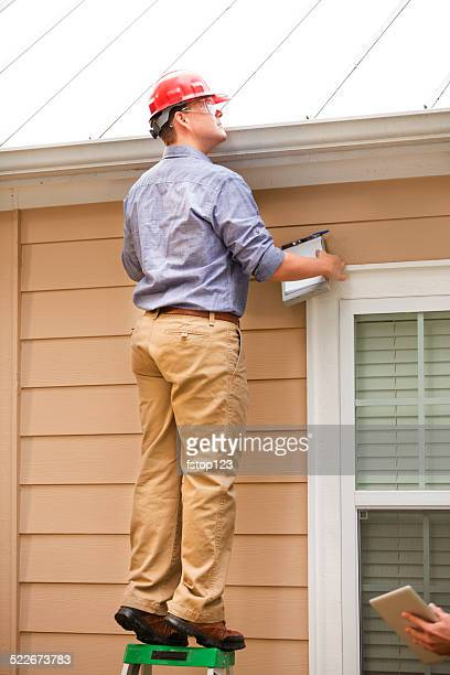 Inspector or blue collar worker examines building roof outdoors.