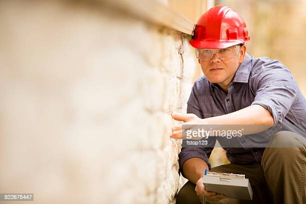 Inspector or blue collar worker examines building wall outdoors.