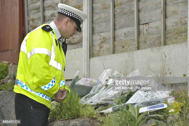 Inspector Rob Pearson Road Policing Department stands by floral tributes on a wall near the pavement where 11yearold Sam Riddall died after a car...