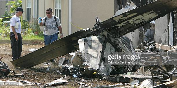 NTSB inspectors look over debris and airplane parts Wednesday July 11 at the scene where a Cessna 310 crashed into two homes in the Preserve at Lake...