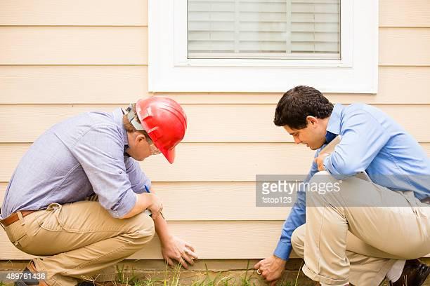 Contrôleurs ou Collier bleu travailleurs examiner bâtiment mur, base.  Plein air.