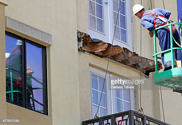 Inspectors who did not want to be identified go up in a cherry picker to get photos and measurements of the rotted wood beams and the lower balcony...