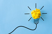 Inspiration and great idea concept. light bulb with crumpled yellow paper on blue background.