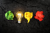 lit lightbulb with crumpled paper balls, idea or inspiration concept