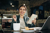 Inspired smiling young woman writing ideas in notepad