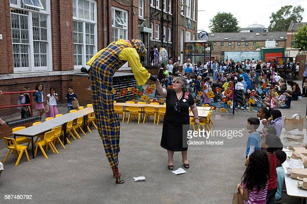 Inspirational head teacher Anna Hassan is greeted by a clown on stilts during a special pupils picnic held at the school to celebrate her recent...
