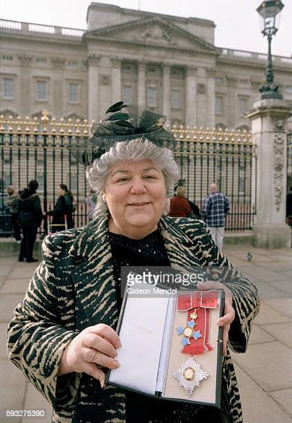 Inspirational head teacher of Millfields Community School Anna Hassan holds her new medal outside Buckingham Palace shortly after she was made a DBE...