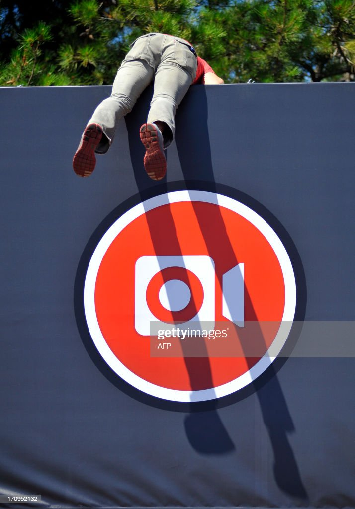 Instagram iOS Engineer Ryan Gomba jumps down from atop the Facebook sign at Facebook's corporate headquarters after a media event in Menlo Park, California, June 20, 2013. Facebook announced June 20th that it will add smartphone video-sharing to its Instagram photo-based social network, in a move that challenges Twitter's popular Vine service. Instagram video apps tailored for iPhones and smartphones powered by Google-backed Android software feature 13 filters for special effects and post to people's Facebook pages the same way pictures do, according to Systrom. AFP PHOTO / Josh Edelson