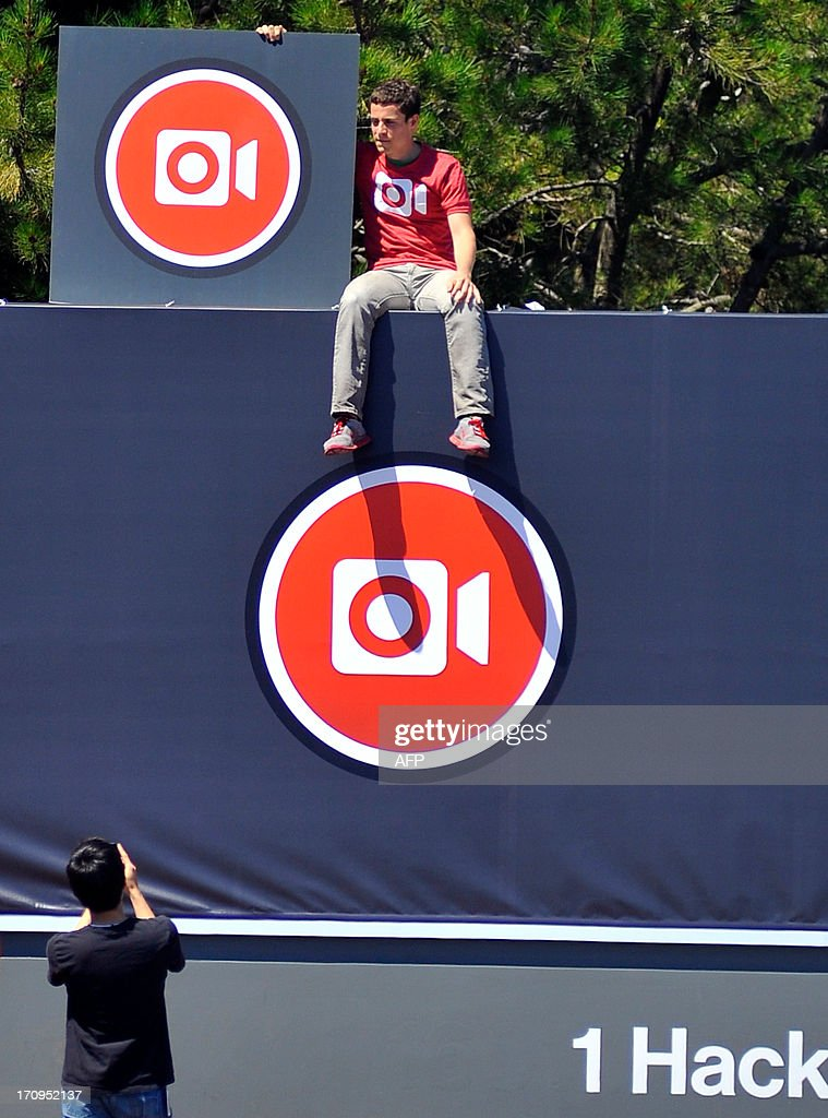 Instagram iOS Engineer Ryan Gomba sits atop the Facebook sign at Facebook's corporate headquarters after a media event in Menlo Park, California, June 20, 2013. Facebook announced June 20th that it will add smartphone video-sharing to its Instagram photo-based social network, in a move that challenges Twitter's popular Vine service. Instagram video apps tailored for iPhones and smartphones powered by Google-backed Android software feature 13 filters for special effects and post to people's Facebook pages the same way pictures do, according to Systrom. AFP PHOTO / Josh Edelson