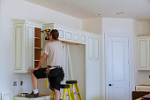 Worker installs doors to kitchen cabinet. Installation of doors on kitchen cabinets