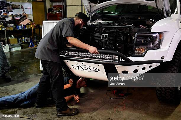 Installer Justin Scrivner lines up a custom skid plate on a 2014 Ford Raptor with help on the bottom end from new guy Luke Maes at FiveR Trucks...