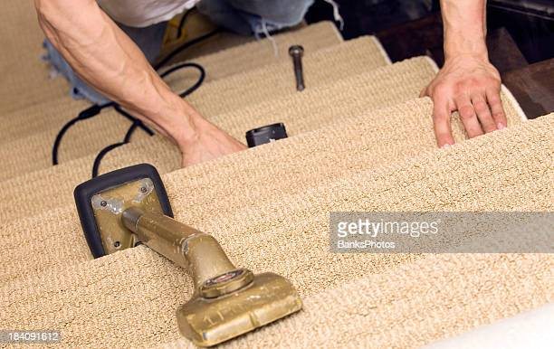 Installer Stapling Stair Carpet with Knee Kicker in the Foreground