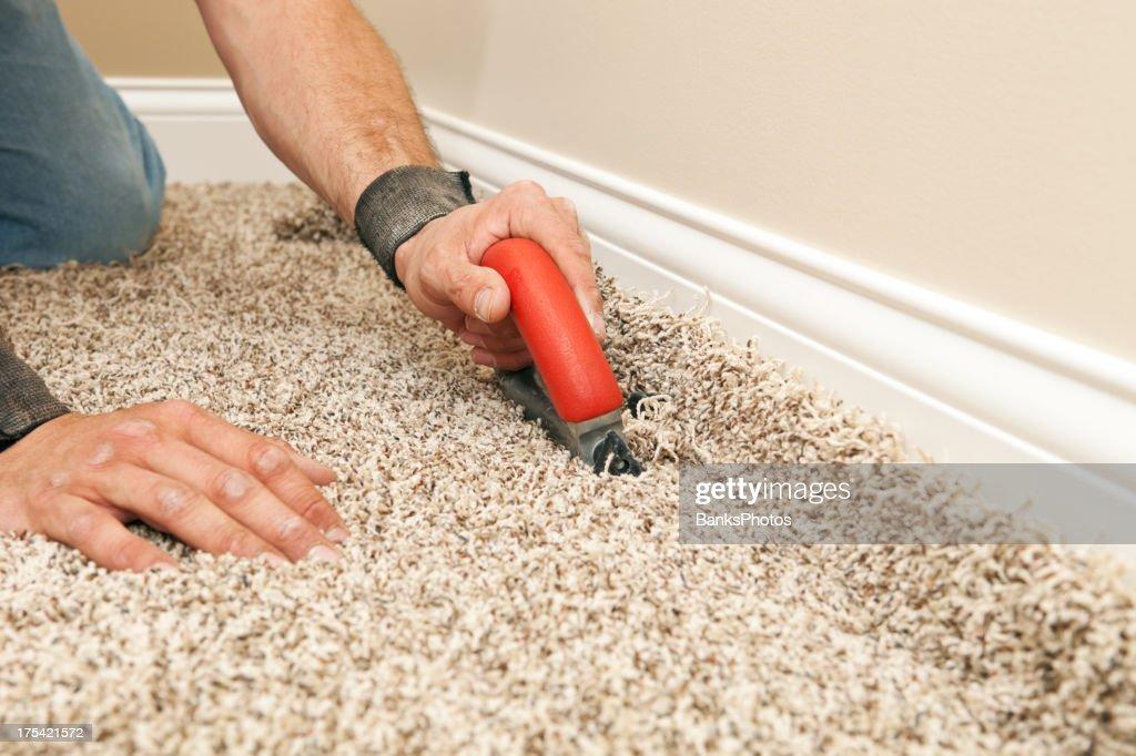installer using carpet cutter on new bedroom floor stock photo
