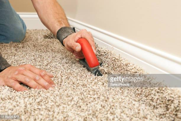 Installer Using Carpet Cutter on New Bedroom Floor
