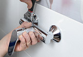 Man's hands fixing a shower faucet with a adjustable wrench.