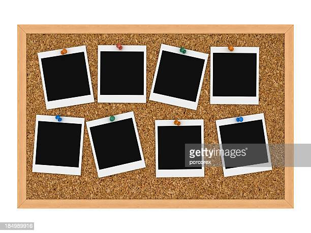 Instant pictures tacked to cork board