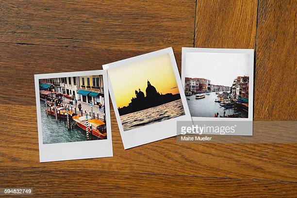 Instant print photographs of famous places on wooden table
