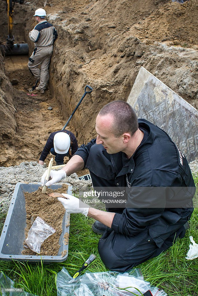 Institute of National Remembrance (IPN) employees work at the scene where human remains of a Stalinist-era mass grave are exhumed on the military cemetary in the heart of the Polish capital Warsaw, May 13, 2013. The grave is believed to contain the remains of around 200 victims of a post-war campaign of communist terror.