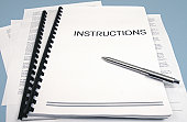 Instruction books and papers with focus on the word 'Instructions.'