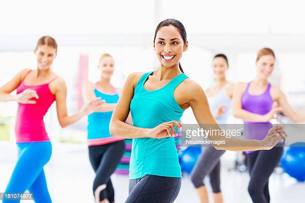 Instructor And Customers Practicing Aerobic Dance In Gym
