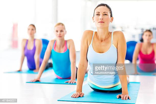 Instructor And Customers Practicing Yoga Exercise In Gym
