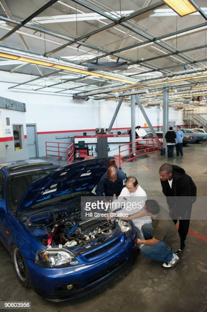 Instructor and students working under engine of car