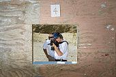 Instructor assisting woman aiming machine gun at firing range