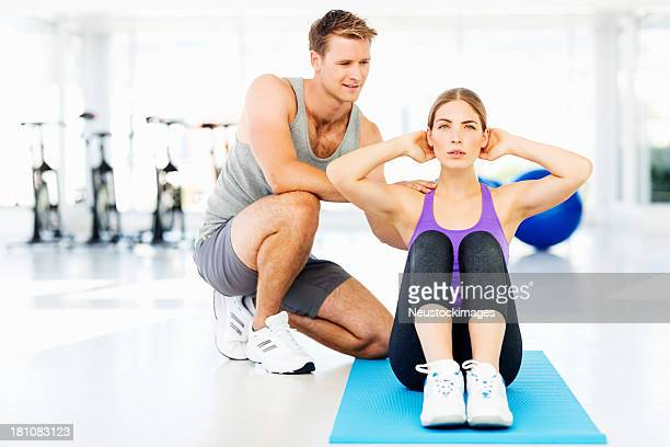 Instructor Assisting Woman In Doing Sit-Ups At Gym