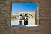 Instructor assisting woman loading gun at firing range in desert