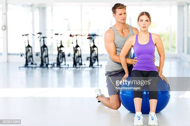 Instructor Assisting Woman Sitting On Fitness Ball At Gym