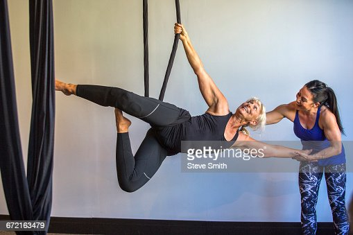 Instructor assisting yoga student hanging from silks