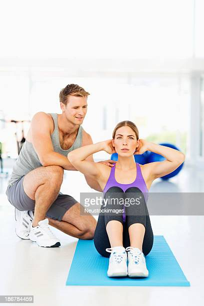 Instructor Assisting Young Woman In Doing Sit-Ups