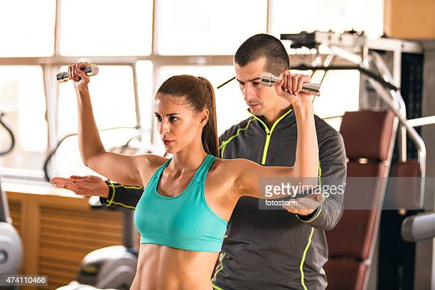 Instructor helping a young woman lift dumbbells in a gym