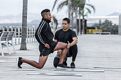 Handsome personal trainer touching knee of lunging African American guy in sportswear during workout on embankment