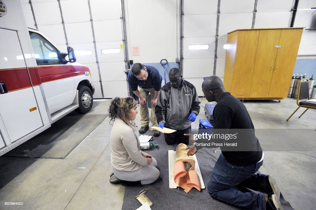 Instructor Paul Froman, back left, looks over students training to become EMT's Thursday, March 9, 2017. Students are Afsaneh Emami of South Portland, originally from Iran, Nicolas Niyonizigiye of Portland and originally from Burundi and David Ngandu of Portland, originally from the Democratic Republic of Congo.